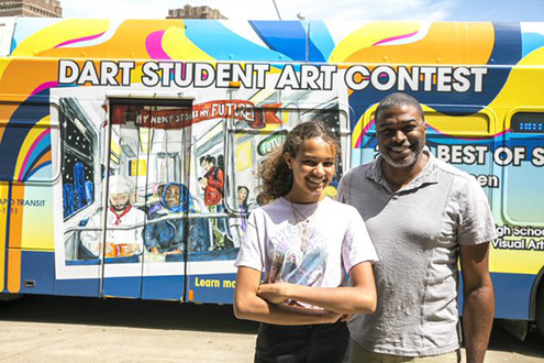 2019 Student Art Contest Winner Sarah Thigpen and her father stand in front of a DART bus wrapped with her artwork