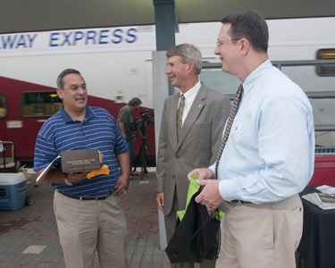 From left to right: On Friday, July 9, Bill Velasco, Chairman of the Board, Dallas Area Rapid Transit; Dick Ruddell, President/Executive Director, Fort Worth Transportation Authority and Gary Thomas, President/Executive Director, Dallas Area Rapid Transit, were on hand at CentrePort/DFW Airport Station to thank customers for riding the Trinity Railway Express. Morning rush hour customers were treated to cookies and gifts from area businesses.