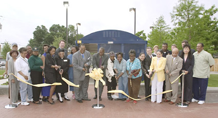 DART President Gary Thomas (back row left), Dallas City Councilman Leo Chaney Jr. (left of bow), and DART Chairman Huelon A. Harrison (third from right) are joined by DART board members and community leaders to celebrate the opening of the Malcolm X Boulevard Transfer Location on Friday, April 23.