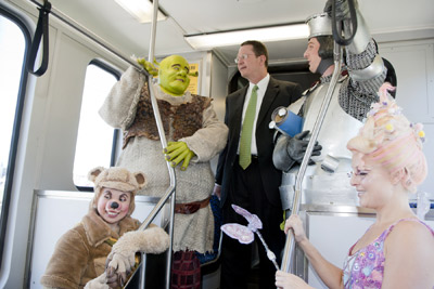 Cast members of Shrek the Musical join DART President/Executive Director Gary Thomas onboard a DART Rail Green Line train to Fair Park Station